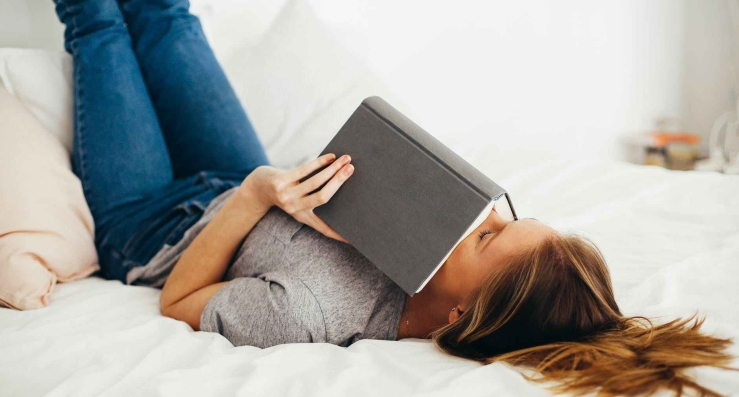 woman lying on bed holding book