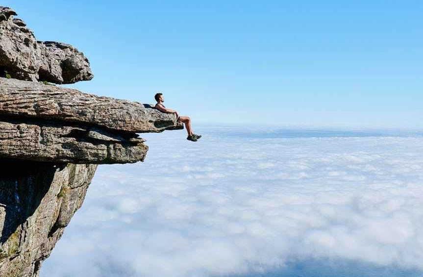 person sitting on mountain cliff